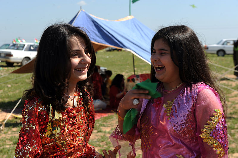 """263827 A pair of girls giggle with one another during a Kurdish New Year celebration in the Qarah Anir region of Kirkuk, Iraq, March 21 in 2010"" by U.S. Navy photo by PO1 Matthew Leistikow -"