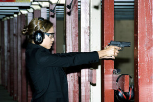 """Rosario Dawson firing a M11 pistol"" by U.S. Air Force photo/Mike Hastings"