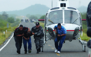 Police take a suspected drug trafficker off a helicopter in Hermosillo in the state of Sonora. Journalists who print names or photographs of cartel members risk their lives. As a result, many papers in Northern Mexico have stopped reporting on drug violence. Image Source: Knight Foundation, Flickr, Creative Commons